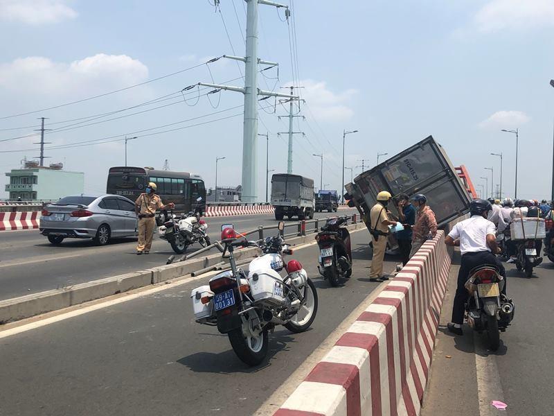 Ô tô tải lao vào làn xe máy, lật trên cầu Bình Lợi - ảnh 1