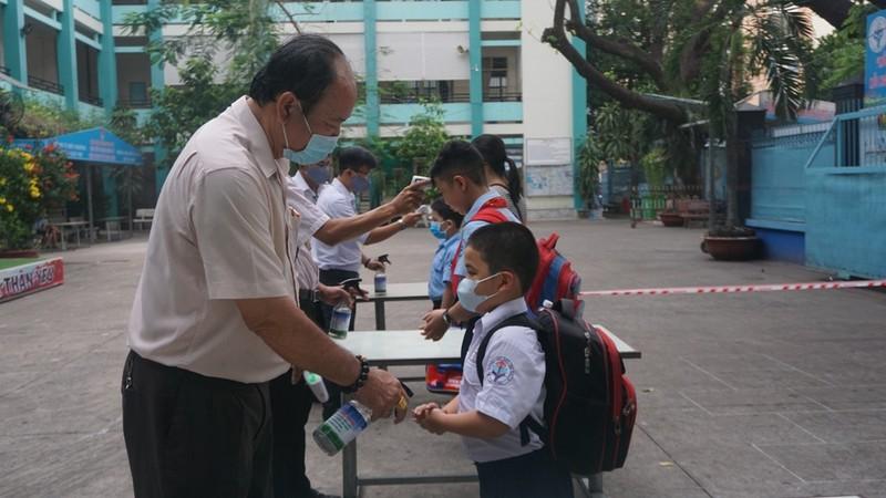 Thầy hiệu trưởng đứng đo thân nhiệt cho học sinh  - ảnh 1