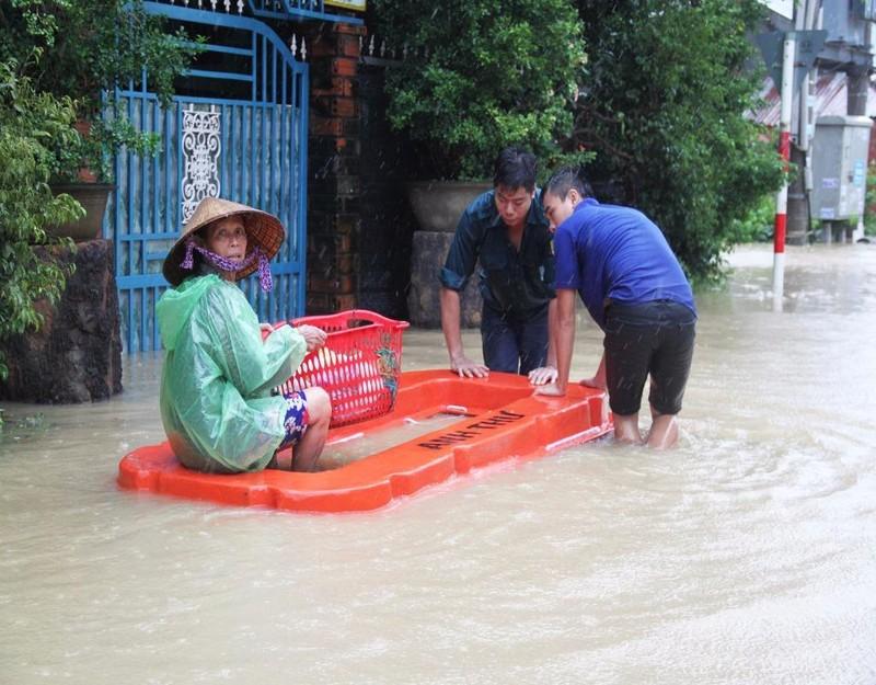 Lực lượng thanh niên xung kích xã Phước Lộc, huyện Tuy Phước (Bình Định) đưa người già đi tránh lũ.