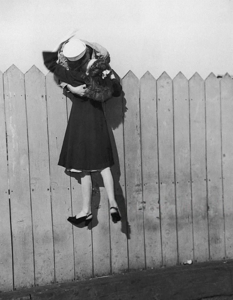 Một thủy thủ cố gắng rướn mình qua hàng rào để nhấc bổng bạn gái lên hôn, 1945